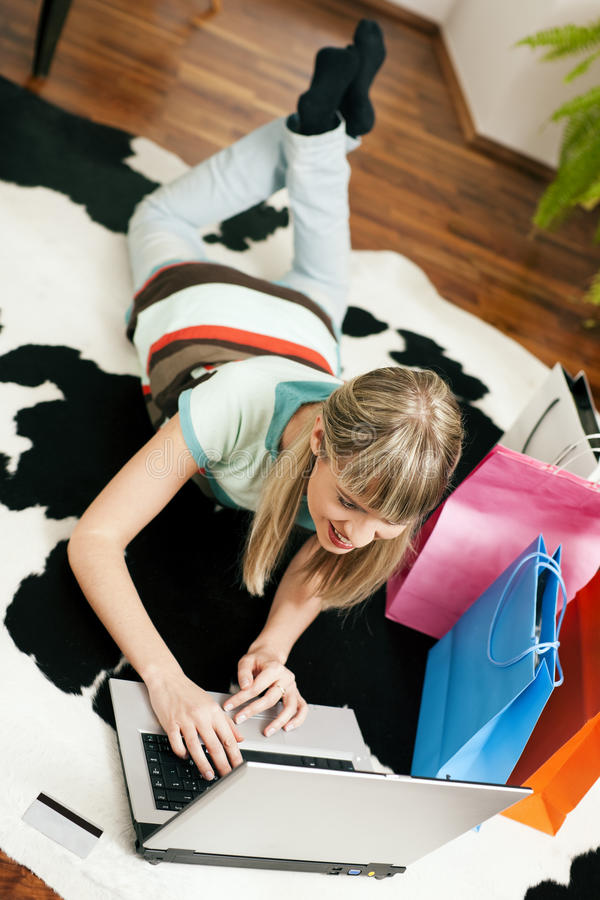 Woman shopping online via Internet from home. Woman lying in her home living room on floor shopping or doing banking transactions online in the Internet stock photos