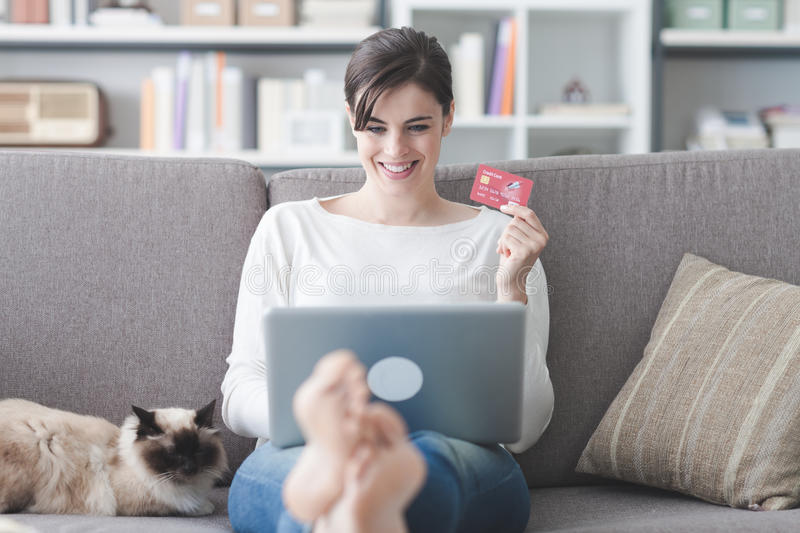 Woman shopping online. Young smiling woman at home, she is relaxing on the couch with her cat and shopping online using a credit card stock photos