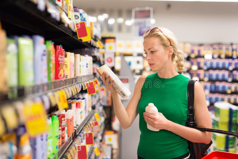 Woman shopping personal hygiene products at supermarket. Beautiful caucasian woman shopping personal hygiene products at supermarket royalty free stock images
