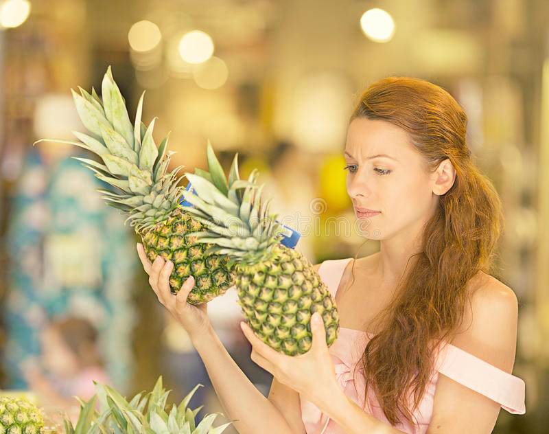 Woman shopping in supermarket, fruit section. Attractive woman shopping in supermarket. Closeup portrait beautiful young woman picking up, choosing fruits stock photo