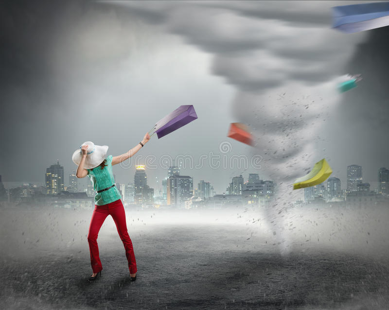 Woman and shopping tornado. Woman stands near tornado with shopping bags stock photography