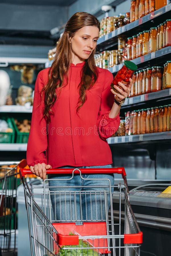 woman with shopping trolley choosing products royalty free stock image