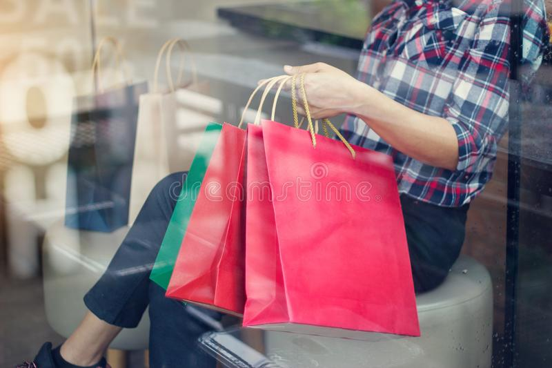 Woman with shoppingbags in hand relaxing in shop of mall stock photography