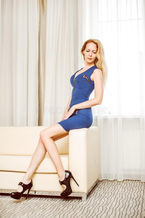 Woman in short blue dress on sofa in white room royalty free stock images