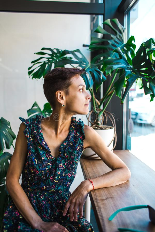 A woman with short hair dreamily looks out the window stock photos