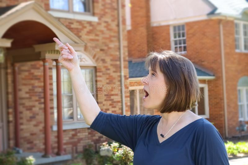 Woman with short hair in front of blurred brick houses points and looks surprised royalty free stock photography