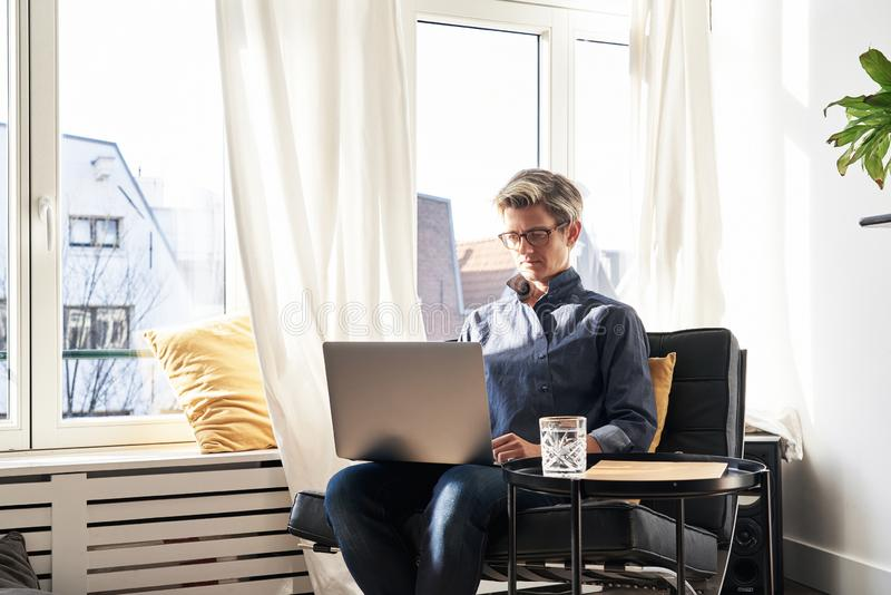 Woman with short hair and glasses working on laptop at modern apartment, opened window, sunny daylight. stock image