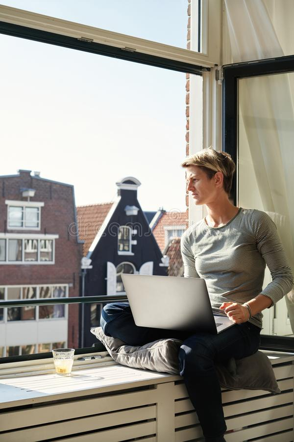 Woman with short hair sitting at window with canal view sill with laptop and coffee, working on a project in private apartment royalty free stock photography
