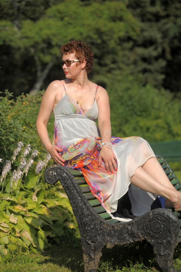 Woman with a short haircut and a long summer sarafan sits stock image