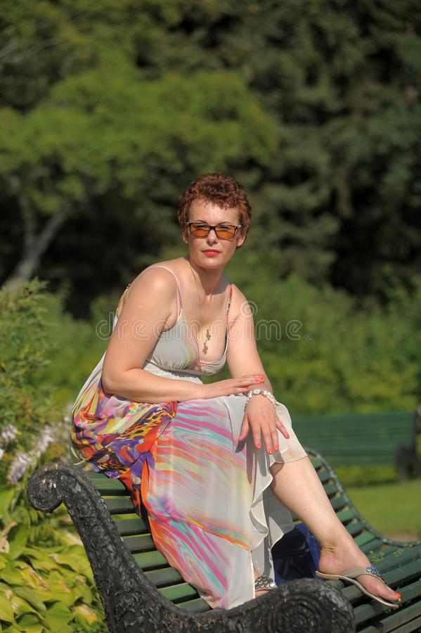 Woman with a short haircut and a long summer sarafan sits royalty free stock images