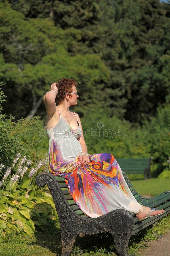 Woman with a short haircut and a long summer sarafan sits stock photo