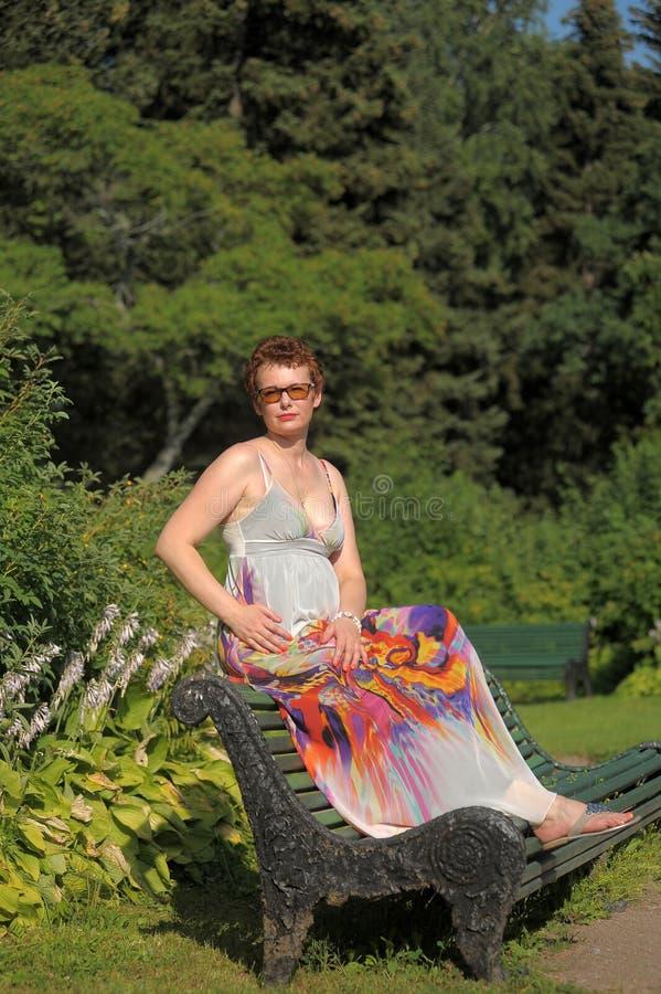 Woman with a short haircut and a long summer sarafan sits royalty free stock image