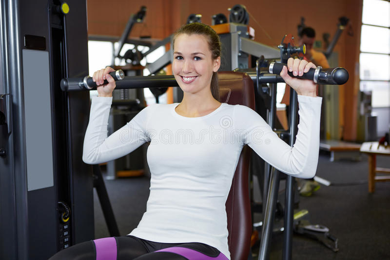 Woman on shoulder press in fitness. Happy young woman exercising on a shoulder press in fitness center stock photos