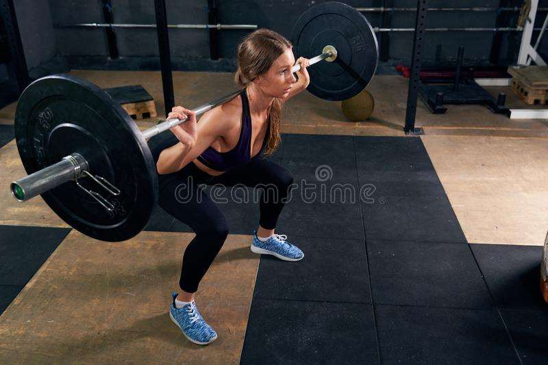 Woman in Shoulder Squat. High angle of strong young woman lifting heavy barbell performing shoulder squat during crossfit workout in modern gym stock photography