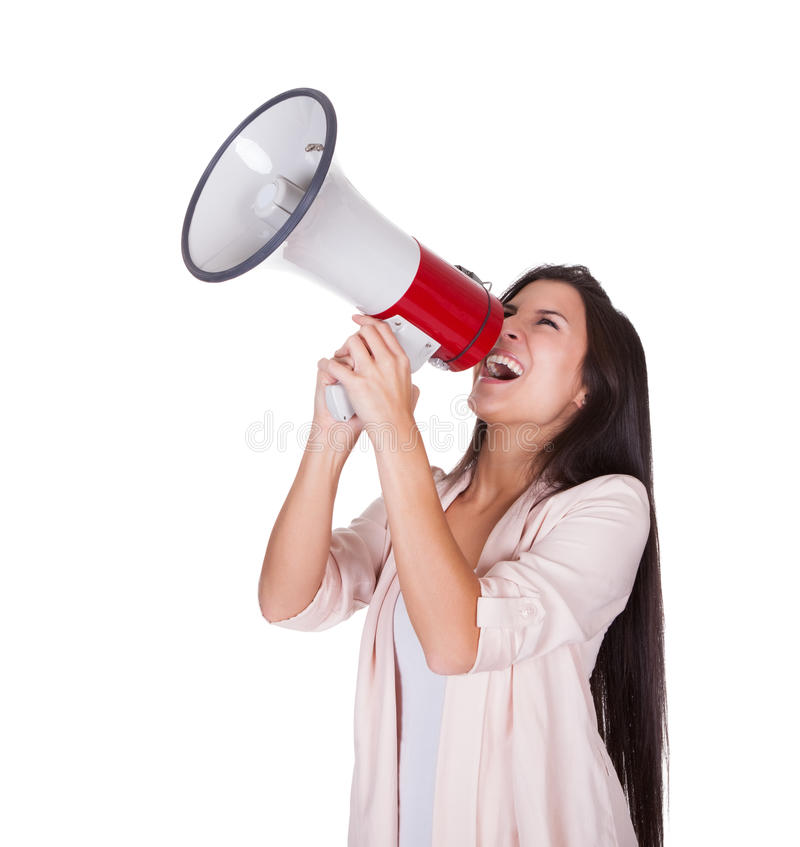 Woman shouting into a loud hailer. Woman holding a loud hailer above her head shouting into it with a passion isolated on white royalty free stock photo