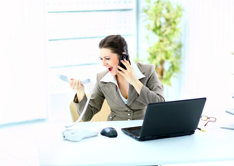 Woman Shouting In Phone In Front Of A Laptop Royalty Free Stock Photos
