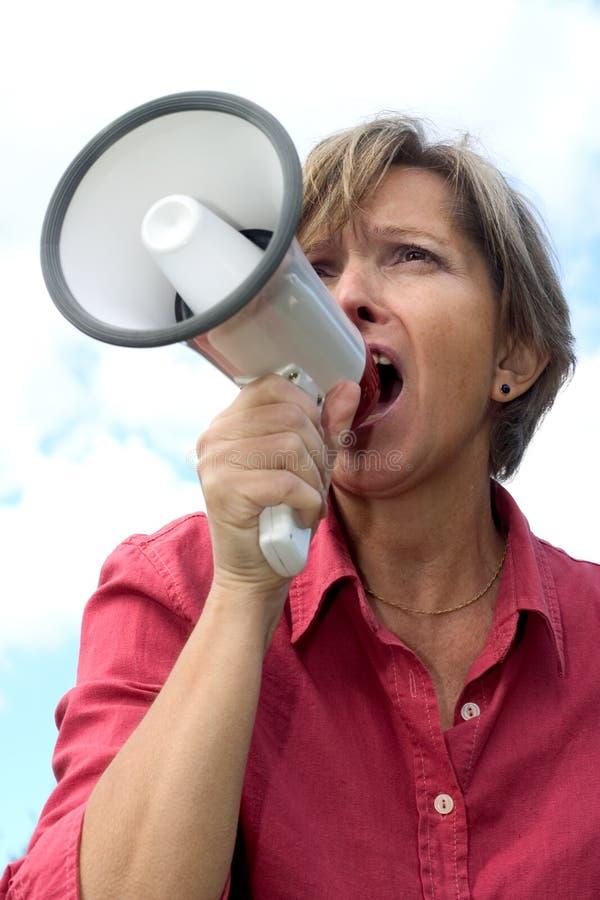 Woman shouts through a megaphone stock photo