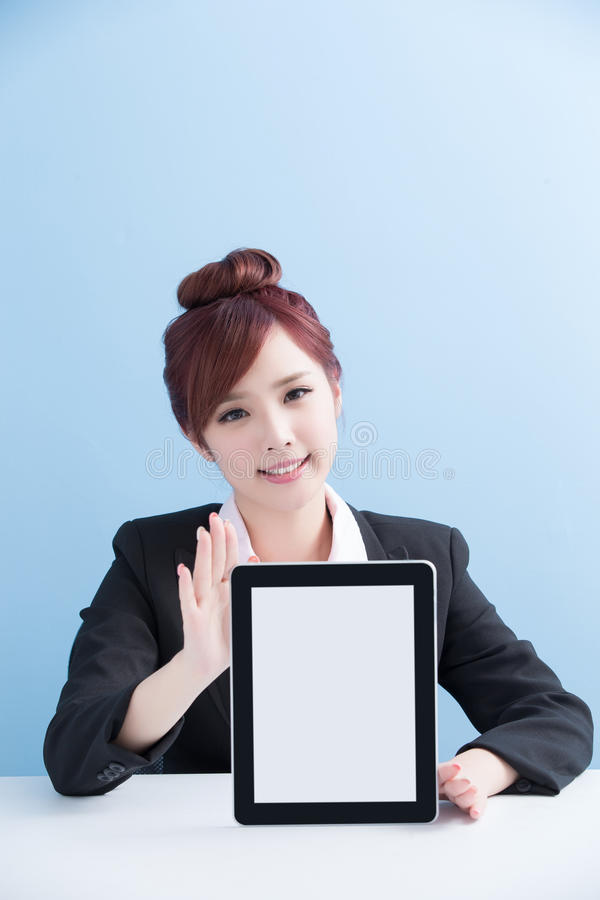 Woman show tablet to you. Business woman show tablet to you with on blue background, asian stock photos