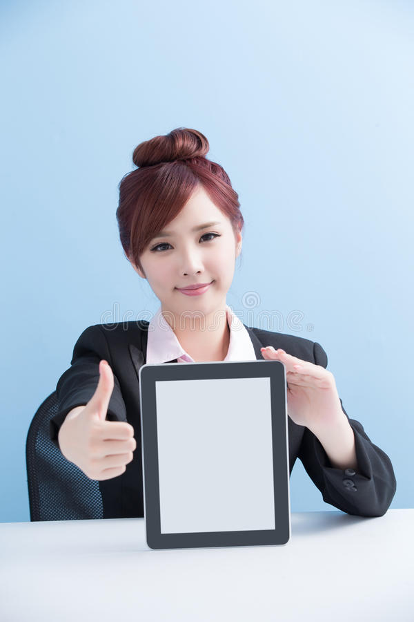 Woman show tablet to you. Business woman show tablet to you and thumb up with isolated on blue background, asian stock photo