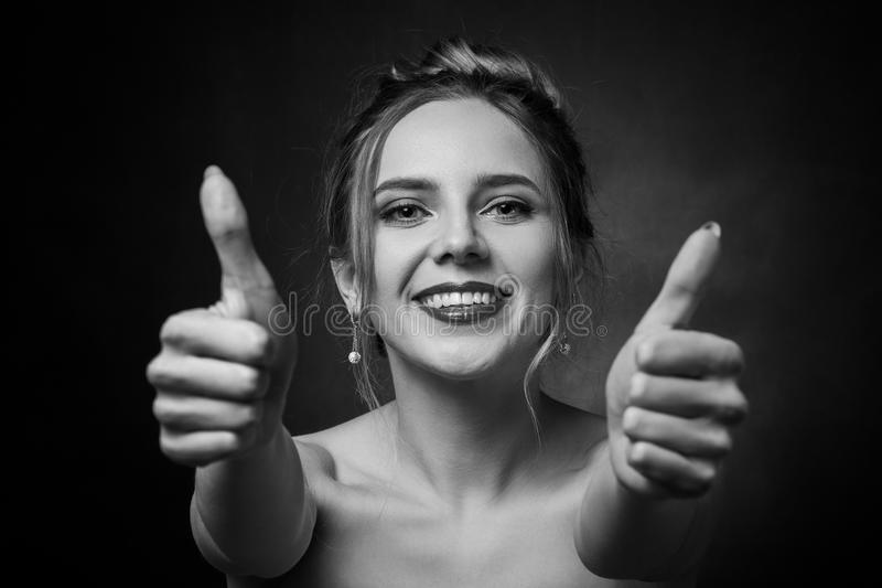 Woman show thumbs. Happy woman shows her thumbs on black background looking at camera laughing, monochrome royalty free stock photography