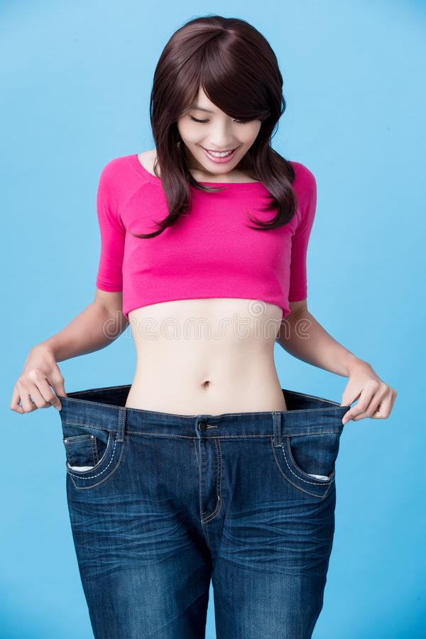 Woman show weight loss. Woman wear jeans and show weight loss with slim waist on the blue background stock photography