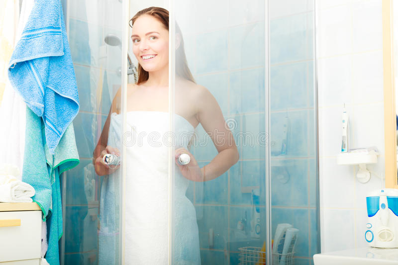 Woman showering in shower cabin cubicle. Girl showering in shower cabin cubicle enclosure. Young woman with white towel taking care of hygiene in bathroom royalty free stock photography
