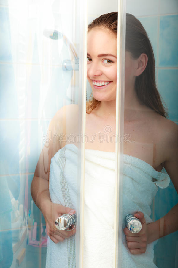 Woman showering in shower cabin cubicle. Girl showering in shower cabin cubicle enclosure. Young woman with white towel taking care of hygiene in bathroom stock images