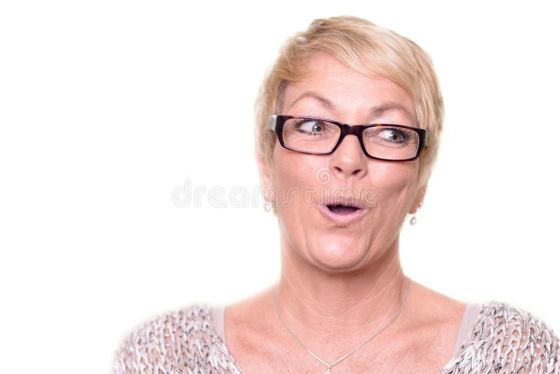 Woman showing appreciative amazement. Attractive middle-aged blond woman wearing glasses showing appreciative amazement or astonishment saying Ooh with an amused royalty free stock photography