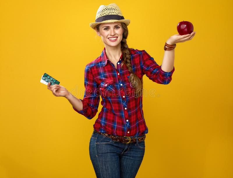 Woman showing benefits of healthy food as opposed to medicine stock photography