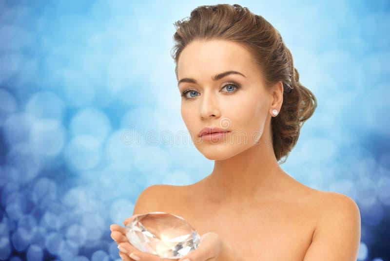 Woman showing big diamond over blue lights stock photography