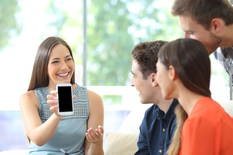 Woman showing blank phone screen to her friends royalty free stock image