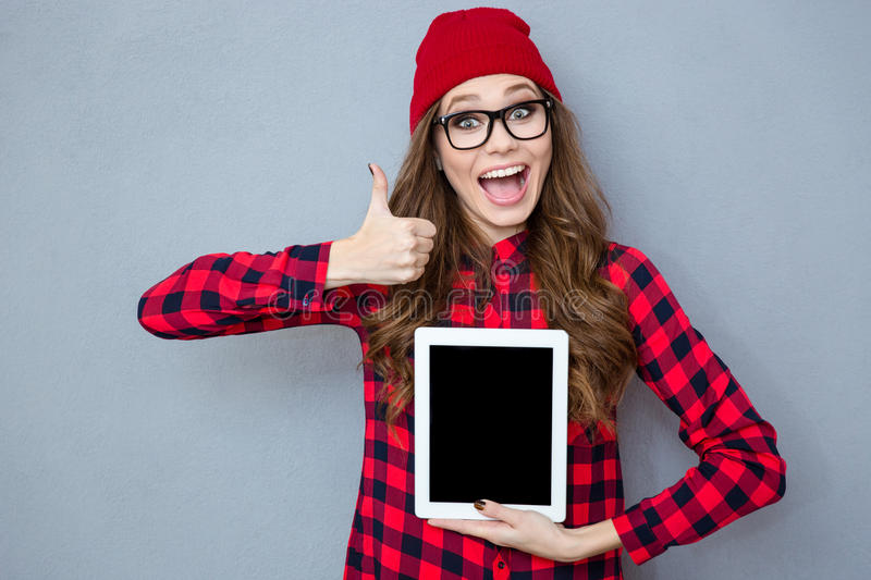 Woman showing blank tablet computer screen and thumb up. Portrait of a cheerful woman showing blank tablet computer screen and thumb up on gray background stock photography