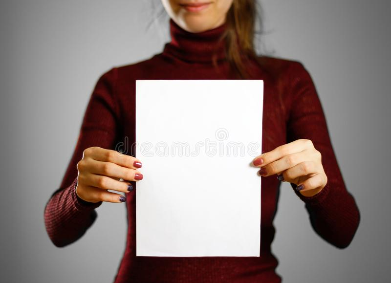 Woman showing blank white flyer paper. Leaflet presentation. Pam. Phlet hold hands. Girl show clear offset paper. Sheet template stock photo