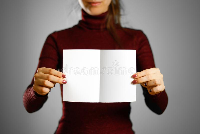 Woman showing blank white flyer paper. Leaflet presentation. Pam. Phlet hold hands. Girl show clear offset paper. Sheet template royalty free stock photography