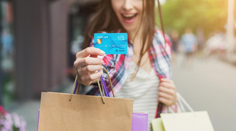 Woman showing credit card and holding shopping bags royalty free stock photo