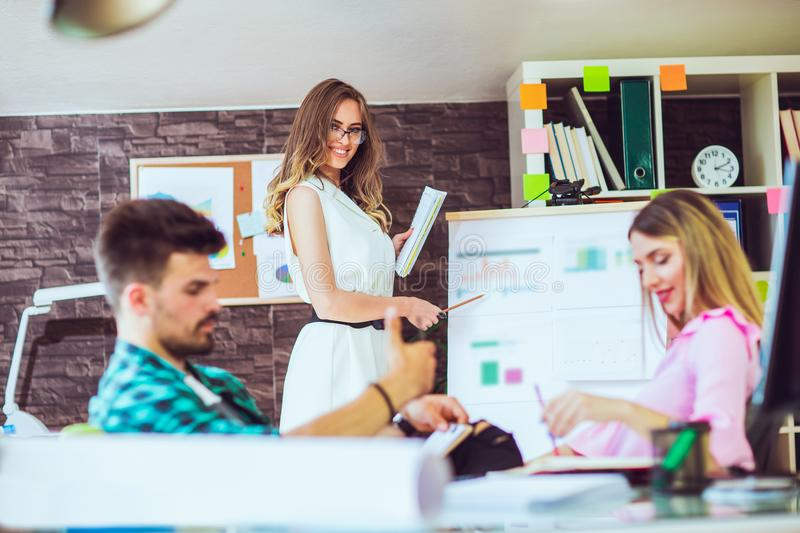 Woman showing diagrams on flipboard. To creative team at office stock photos