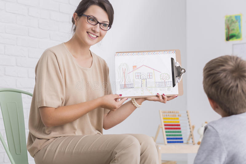 Woman showing drawing to child royalty free stock photography