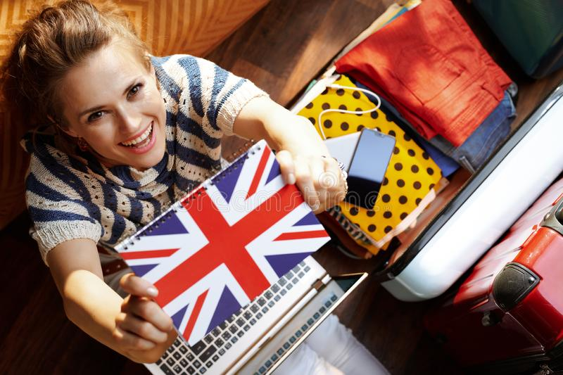 Woman showing Great Britain flag notebook while buying ticket. Upper view of happy modern woman in white pants and striped blouse in the modern living room in royalty free stock photography