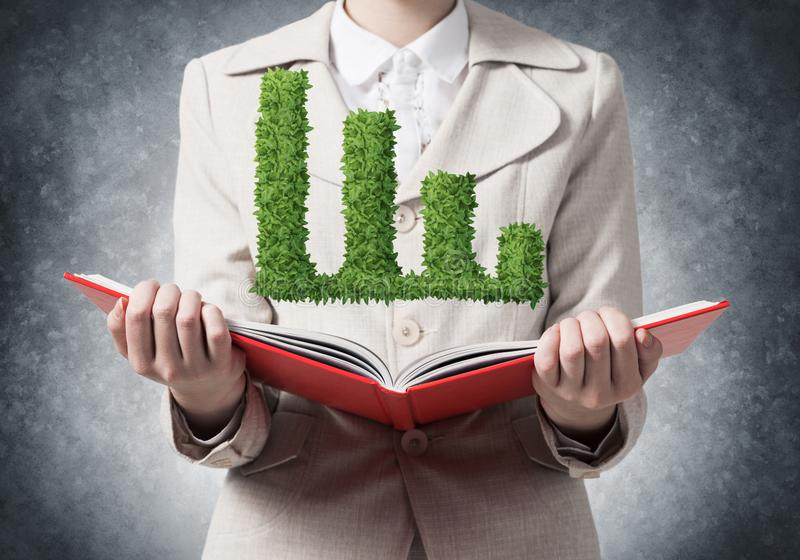 Woman showing green plant in shape of graph. Businesswoman showing green plant in shape of growth financial graph above opened notebook. Business presentation stock photography