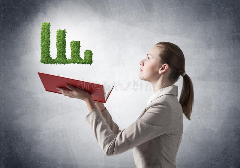 Woman showing green plant in shape of graph. Businesswoman showing green plant in shape of growth financial graph above opened notebook. Business presentation royalty free stock photo