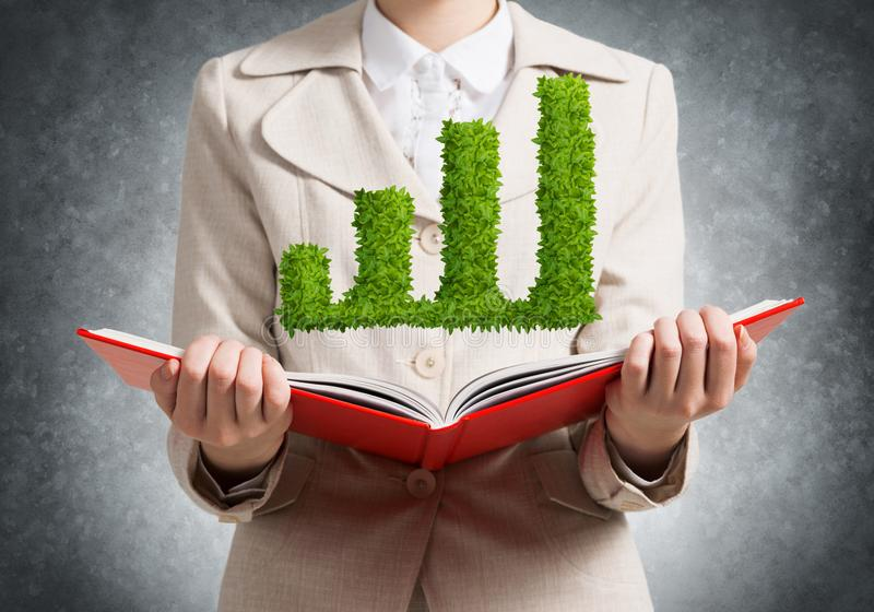 Woman showing green plant in shape of graph. Businesswoman showing green plant in shape of growth financial graph above opened notebook. Business presentation stock photo