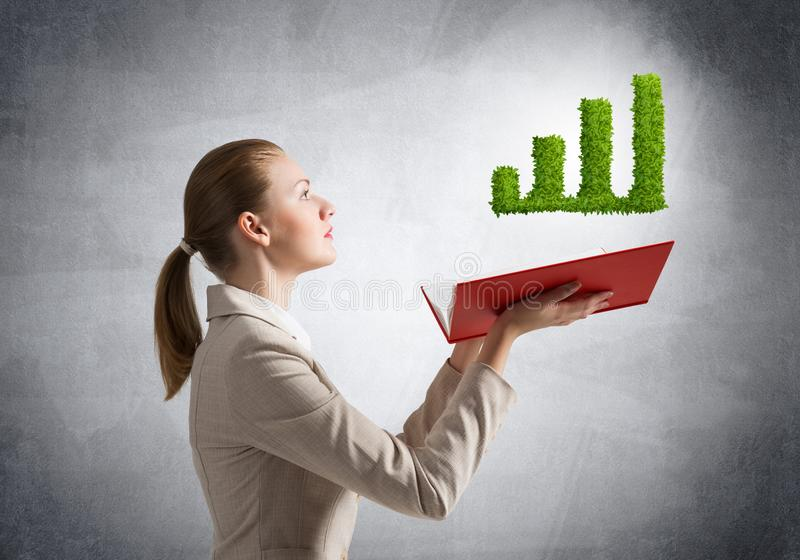 Woman showing green plant in shape of graph. Businesswoman showing green plant in shape of growth financial graph above opened notebook. Business presentation stock photos