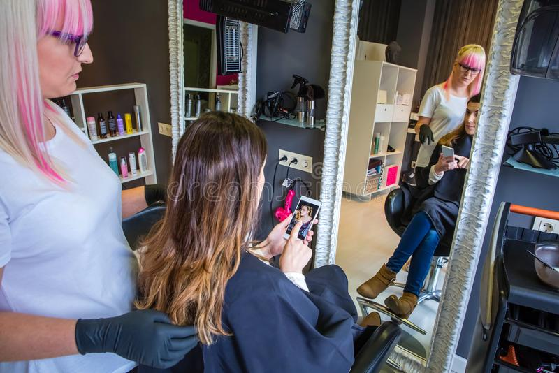 Woman showing hairstyle photo in smartphone to hairdresser stock photos