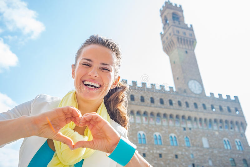Woman showing heart gesture shaped hands, Italy. Happy young woman showing heart gesture shaped hands in front of palazzo vecchio in florence, italy royalty free stock photos