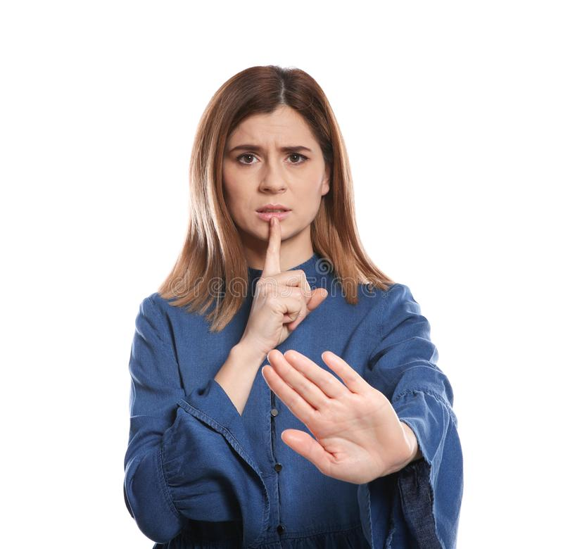 Woman showing HUSH gesture in sign language on background royalty free stock image
