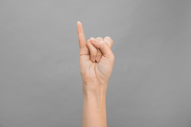 Woman showing I letter on grey background. Sign language stock photo