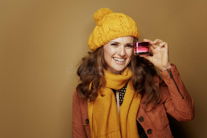 Woman showing jar of facial creme against brown background stock images