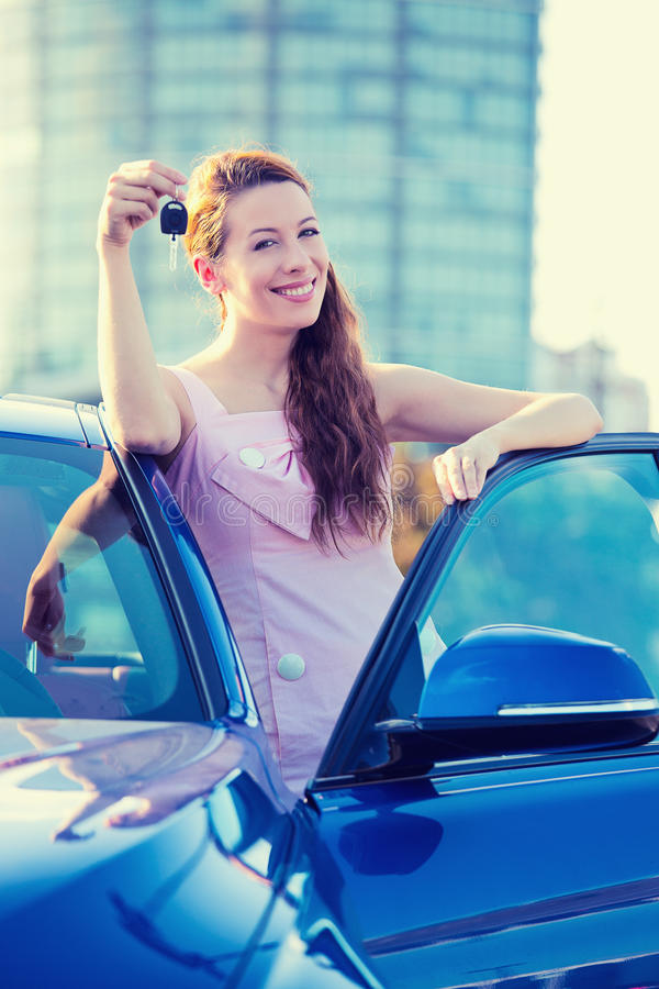 Woman showing keys of new car. Portrait happy smiling young attractive woman buyer standing next to new blue car showing keys isolated outside dealer, dealership stock photo