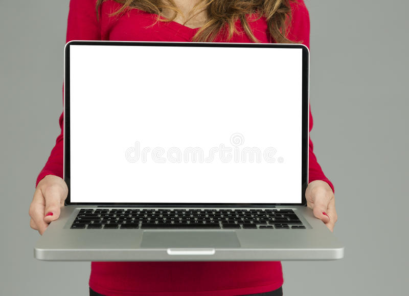 Woman showing laptop with copy space. Woman showing white blank laptop display with copy space on grey background royalty free stock photos