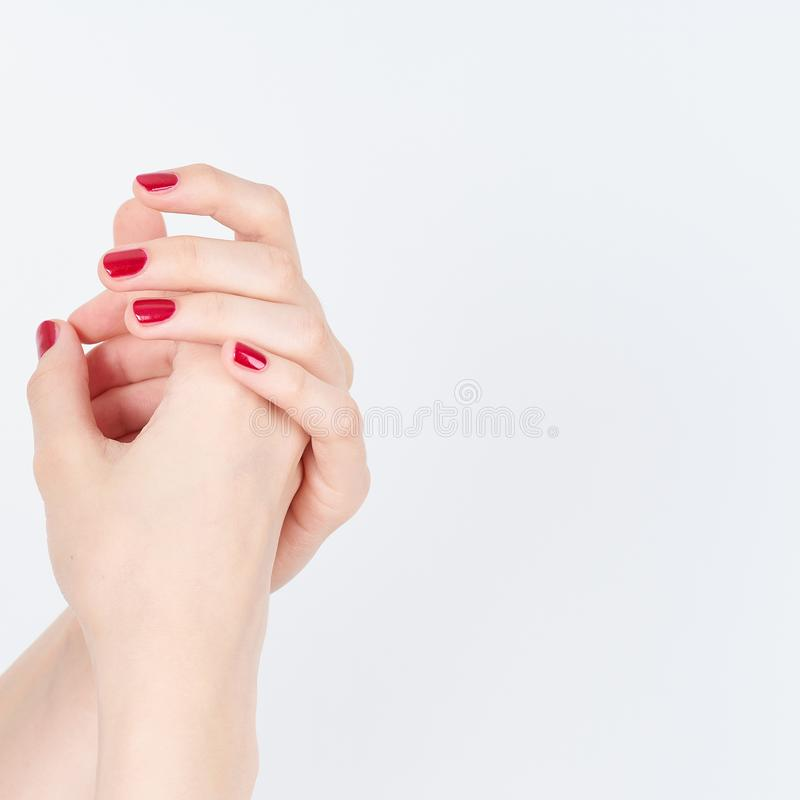 Woman showing manicures hands with red nail polish on white background copy space stock image